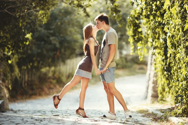Teen couple kissing at street