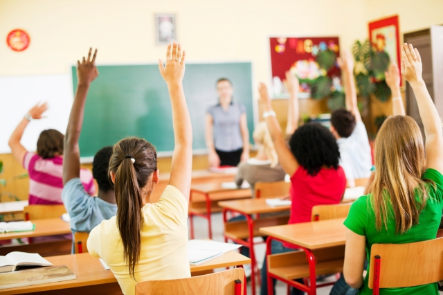 Group of teenagers sitting in classroom with raised hands.