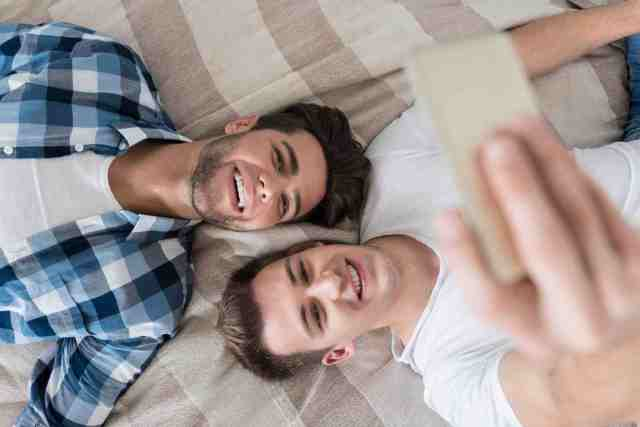 Delighted gay couple making selfie in bed